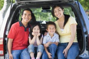 family of 4 sitting in back of van